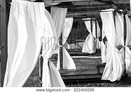 Summer wooden gazebo with a white cloth in the garden.
