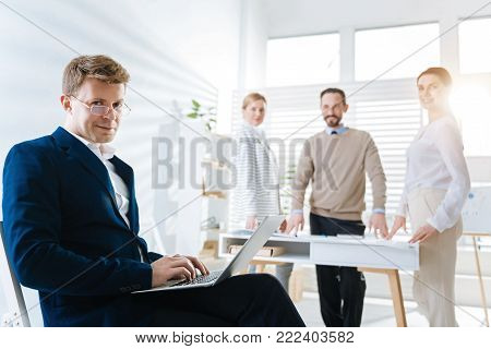 Business correspondence. Earnest mysterious male colleague sitting while holding laptop on knees and looking at the camera
