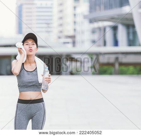 Wiping sweat Thirsty female jogger drinking fresh water after training. Young athletic woman exercising in the city park outdoors. poster