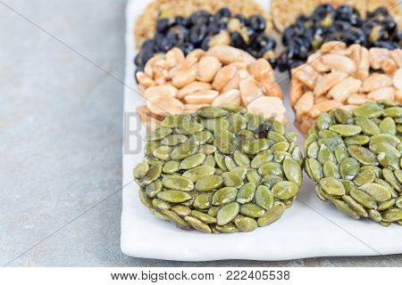 Korean traditional sweet snacks with peanuts, pumpkin seeds, black soybeans and chinese buckwheat on a white plate, horizontal, copy space. Healthy energy snacks