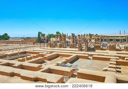 The building of Persepolis Treasury located behind the buildings' foundations and is neighboring with ruined palaces of the complex, Iran.