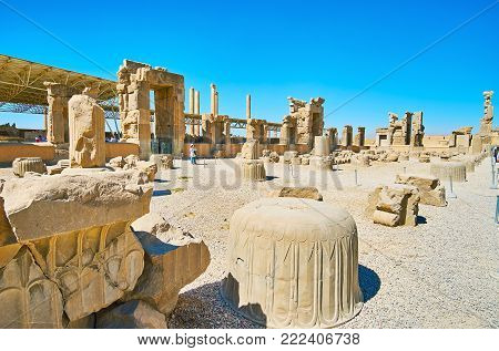 PERSEPOLIS, IRAN - OCTOBER 13, 2017: The ruins of the Hundred Columns Hall with reserved gates, columns' capitals, decorated with reliefs and patterns, on October 13 in Persepolis.