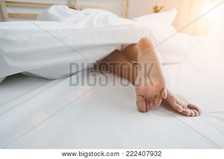 Barefoot Of Human On Bed In Morning. Single And Working People Concept. Lazy Day And Happiness Home