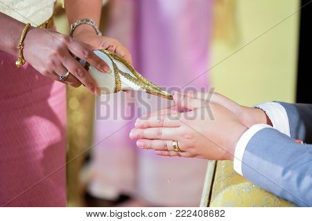 Pouring water from the conch shell into the bride's hands at a Thai wedding.