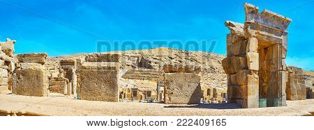 Panorama of Persepolis archaeological site with the view on Artaxerxes III tomb on the rocky slope of Rahmet Mount, seen behind the ruins of Hundred Columns Hall, Iran.