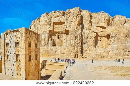 NAQSH-E RUSTAM, IRAN - OCTOBER 13, 2017: The mausoleums, cut in Hossein Mount and Ka'ba-ye Zartosht tower on the foreground, Naqsh-e Rustam Necropolis, on October 13 in Naqsh-e Rustam.