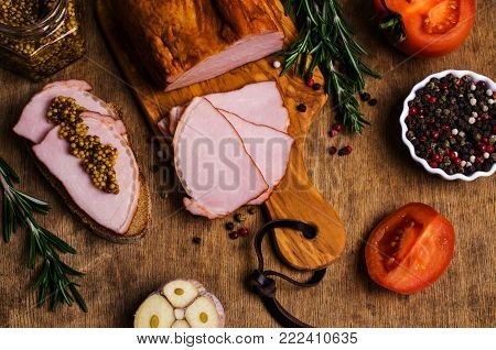 Large piece of smoked meat with vegetables and spices on the old wooden background. Selective focus.