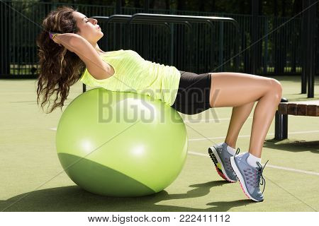 Training on the fit ball. Young woman doing sports exercises on the ball for training. Sporty appearance, a beautiful figure. Exercising fitness