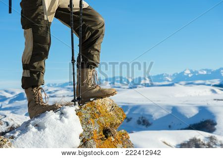 Close-up of a tourist's foot in trekking boots with sticks for Nordic walking standing on a rock stone in the caucasian mountains