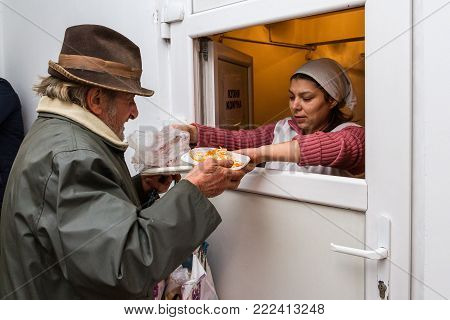 Berehove, Ukraine - December 14, 2017: The poor old man receives a hot lunch in public kitchen for poor and homeless people.