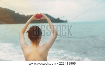 A white woman with hearth hand symbol with sea background