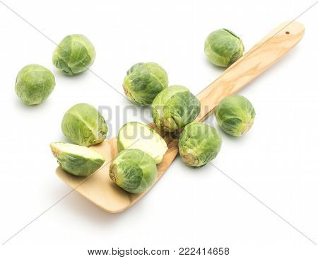 Raw Brussels sprout heads with an olive spatula top view isolated on white background