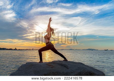 Healthy yoga woman lifestyle exercising vital meditate and energy yoga on the rock near the seashore, sunset background. Healthy Concept.