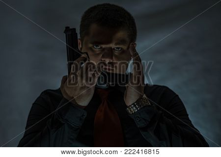 The criminal holds a gun in his hand. The muzzle of the pistol is pointed upwards. Mafia.
