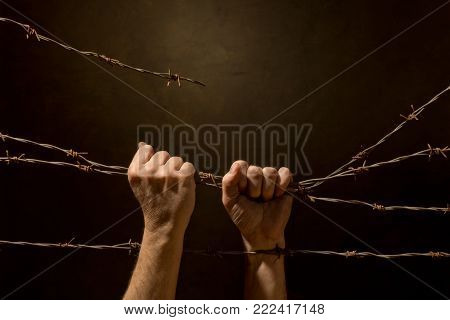 Man Be Handing Fence from Barbed Wire