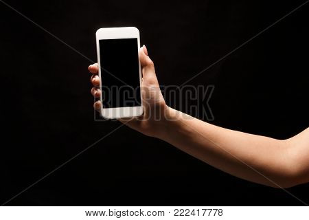 Female hand holding mobile smartphone with blank screen, isolated on black background. Copy space for advertisement of mobile app, mockup