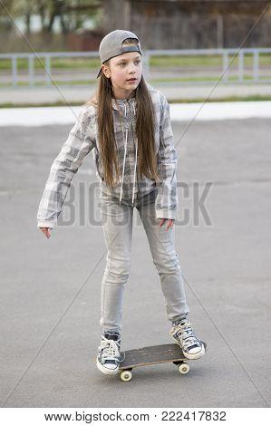 girl riding skateboard on empty parking place