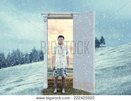 Young in summer clothes  in front opened door on a field during winter which leads to a warmer season. Changing season through the door concept.