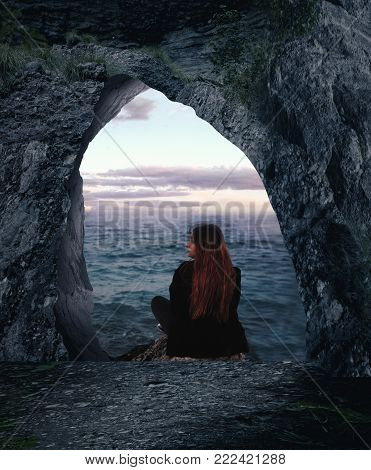 Cave in the mountains leading to the sea, girl sitting on rock and admires the ocean.