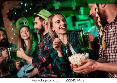 A man in a funny hat and a girl are drinking beer together and eating popcorn. They celebrate St. Patrick's Day with friends. They have fun at the bar.