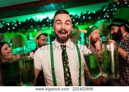 The barman is holding glasses with beer in his hands. He works in the pub. He is wearing suspenders.
