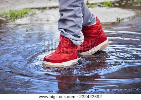 Happy Funny Child Girl Jumping On Puddles In Rubber Boots (happy Childhood, Weather, Rain Conception