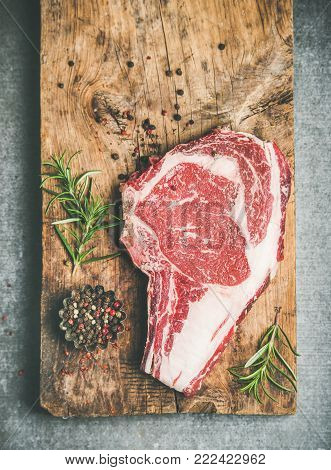 Flat-lay of raw prime beef meat dry-aged steak rib-eye on bone over rustic wooden board over grey concrete countertop background with seasoning, top view, copy space. Meat high-protein dinner concept