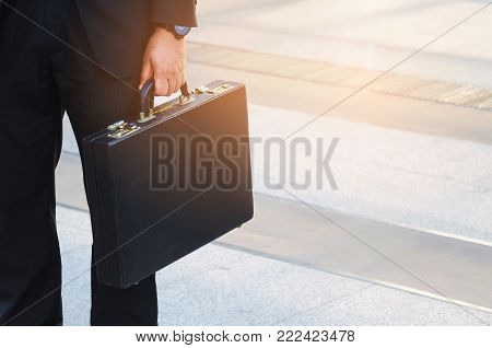 close up of business man in suit holding black briefcase going to work time at morning in modern city, determination, confidence, corporate, lifestyle, rush hour, grow up and successful concept
