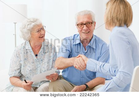 Happy senior couple sealing with an handshake a contract for the retirement