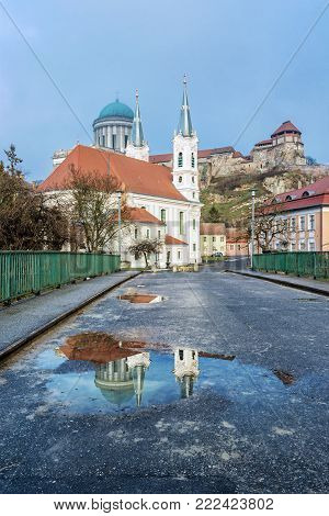 Saint Ignatius church and monumental basilica with reflection in rain water, Esztergom, Hungary. Travel destination. Cultural heritage. Religious architecture.