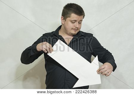 AA white arrow in the hands of a man on a white background. The arrow points down. On a white background.