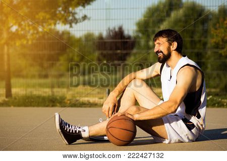 The smiling basketball player with basketball ball is sitting down on playground at the street outdoors and resting.