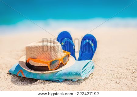 Sandy beach with towel, hat  and summer accessories with copy space.   Vacation and travel items. Tropical Holiday Background