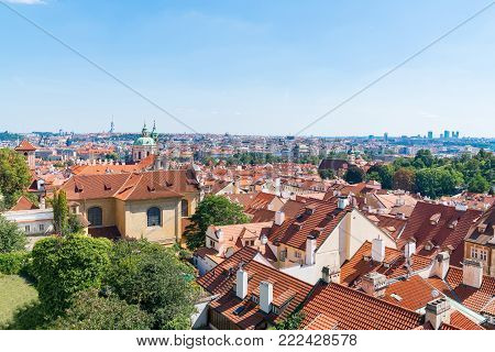 View across orange rooftops of Prague and distant domes, spires and city uildings under blue sky.