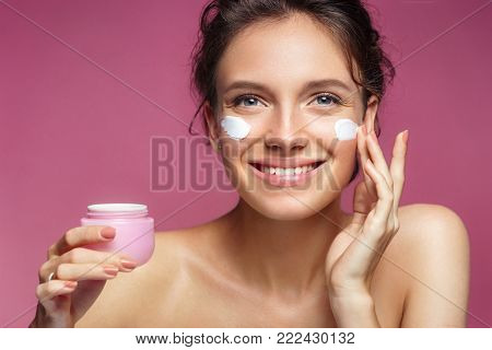 Woman applying wrinkle cream or anti-aging skin care cream. Photo of smiling woman with healthy skin on pink background. Skin care concept