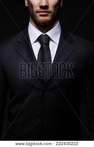 closeup portrait of young handsome businessman isolated on dark studio background