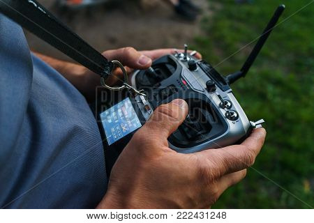 man holds a remote control during the flight control of a sports drones, a scale model of a car. modern technologies and entertainment