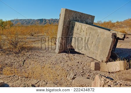 The broken concrete remnants of the Ambrosia Mine located just south of Aguila Arizona. The mine processed Manganese in the 1950s but then shut down in the 1960s. The site has been abandoned since that time.