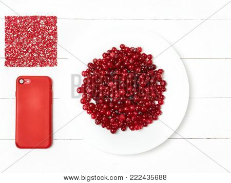 bowl of cowberries on old wooden table and red phone