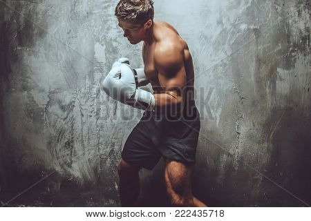Muscular shirtless fighter showing his skills in studio over grey background.