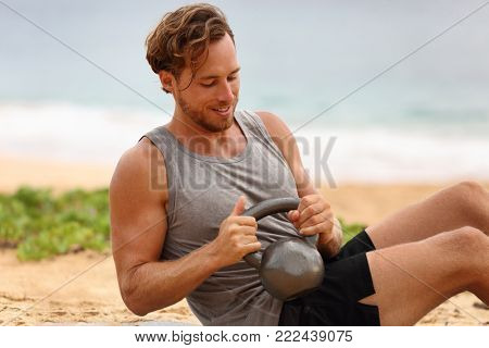 Russian Twist exercise fitness man exercising on beach training with kettlebells working out core, obliques and abdominal muscles. Male fitness instructor doing abs exercise working out six pack.