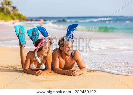 Beach couple snorkel people on summer snorkeling travel holiday watersport leisure activity. Young adults enjoying vacation relaxing lying down on sand near water after swim.