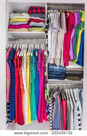 Home closet organized walk-in bedroom wardrobe of women fashion clothes hanging on racks. Summer style, dresses and t-shirts