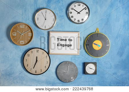 Clocks and frame with phrase TIME TO ENGAGE hanging on wall