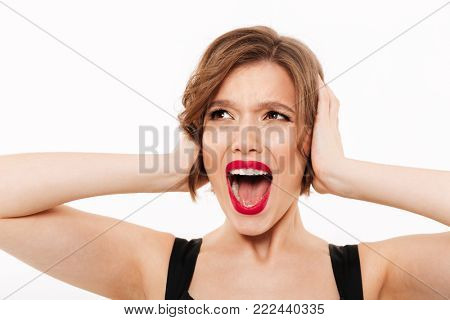 Close up portrait of a furious girl screaming isolated over white background