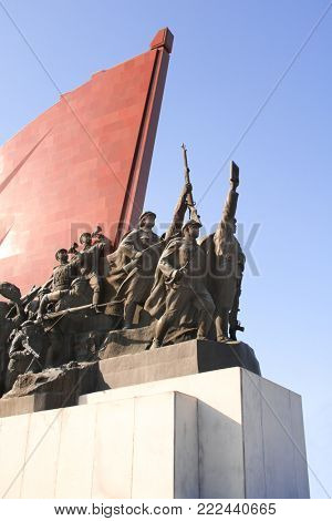 PYONGYANG, NORTH KOREA (DPRK) - SEPTEMBER 14, 2017: Grand Monument Mansudae. Statues of revolutionary people (men, women, children, soldiers, workers) with national flag