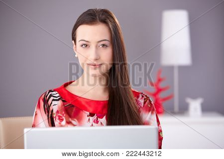Beautiful young woman in red kimono working on laptop computer, looking at camera, smiling.