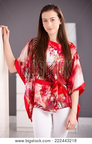 Beautiful young woman standing in red kimono, looking at camera, smiling.