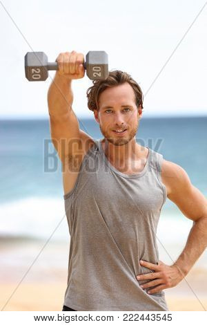 Fitness man training shoulder lifting dumbbell on beach doing Front Dumbbell Raise i.e. Alternating Front Raise exercise for shoulders working out on beach.