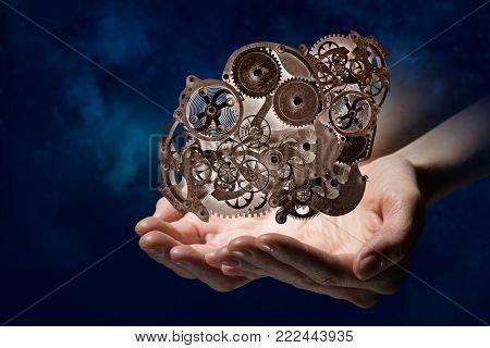 Cogwheel mechanism in hand. Mixed media